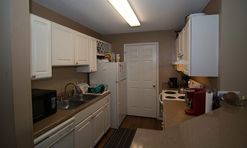 kitchen with white cabinets at a sober living home for men